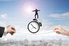 Two hands pulling rope businessman balancing on alarm clock Royalty Free Stock Photography