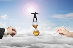 Two hands pulling rope businessman balancing on hourglass Royalty Free Stock Image