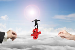 Two hands pulling rope businessman balancing percentage sign. Two hands pulling rope with businessman balancing on red percentage sign, on sun sky cityscape stock photo