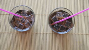 Two hands put two glasses of cola with ice. On the beech wood sticks stock video