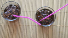 Two hands put two glasses of cola with ice. On the beech wood sticks stock footage