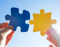 Hands with puzzle pieces. Two hands with puzzle pieces royalty free stock image