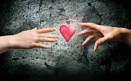 Two hands reach for the heart symbol. royalty free stock photos