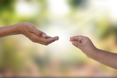 Two hands reaching out. On blurry natural background