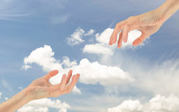 Two hands reaching out to each other. Concept of religion and God. Two hands reaching out to each other on the background of the cloudy sky