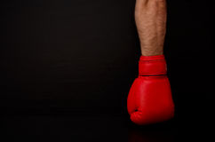 Two hands in red boxing gloves in the side of the frame on a black background,  empty space Royalty Free Stock Images