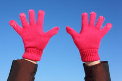 Two hands in red gloves against sky Stock Images