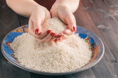 Two hands with rice grains over plate Royalty Free Stock Photography