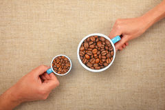 Two hands with roasted coffee beans in cups. Two hands, man and woman, holding small and big cups full with roasted coffee beans together over linen canvas Stock Photos