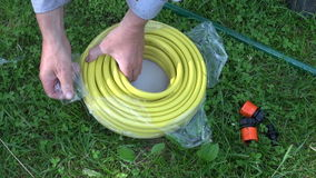Two hands rolling out new yellow water hose. In meadow stock video footage