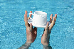 Two hands saving a cup and saucer Royalty Free Stock Photo