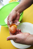 Two hands separating eggwhite from yolk over green Stock Photo