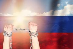 Two hands shackled a metal chain on the background of the Russia flag. Freedom concept.  royalty free stock images