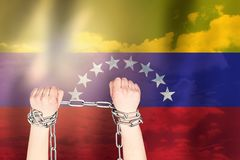 Two hands shackled a metal chain on the background of the Venezuela flag. Freedom concept.  stock images