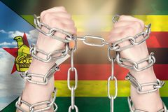 Two hands shackled a metal chain on Zimbabwe flag. Freedom concept.  stock photography