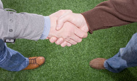 Two hands shaking on grass background royalty free stock photos