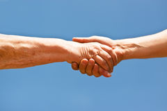 Two hands shaking hands over blue sky Royalty Free Stock Photos
