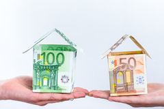 Two hands showing euro bills houses. Two hands showing euro notes model houses isolated on grey white background Royalty Free Stock Photos
