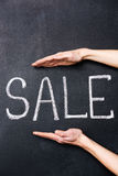 Two hands showing sale written on chalkboard Royalty Free Stock Images