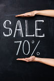 Two hands showing seventy percent sale drawn on blackboard. With chalk Stock Images