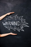 Two hands showing warning drawn on blackboard Royalty Free Stock Image