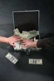 Two hands and suitcase with dollars. On dark Royalty Free Stock Photos