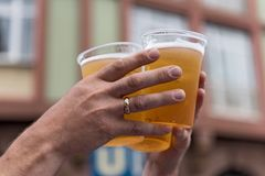 Two hands and three full plastic cups with beer.  stock image