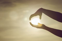 Two hands to holding a sun on sunset moment,hoping concept,fighting,think big concept Royalty Free Stock Images