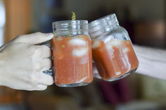 Two hands toasting & x28;cheers!& x29;. With bloody mary drinks Stock Images