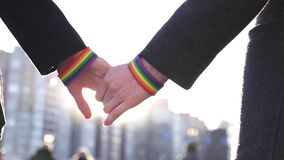 Two hands together with LGBT bracelets against the background of the street and the sun. Slow mo stock video