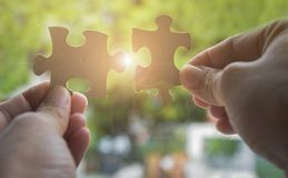 Two hands trying to connect couple jigsaw puzzle piece with sunlight effect. Business solutions, success and strategy concept Stock Photo