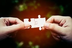 Two hands trying to connect couple puzzle piece with forest background. One part of whole; symbol of association and connection for business strategy Royalty Free Stock Image