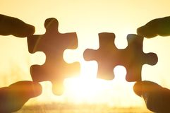 Two hands trying to connect couple puzzle piece with sunset background. Jigsaw alone wooden puzzle against sun rays. Close-up. Teamwork, partnership, business Stock Photography