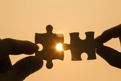Two hands trying to connect couple puzzle piece with sunset background.   symbol of association and connection. Concept of Business Collaboration Royalty Free Stock Photos