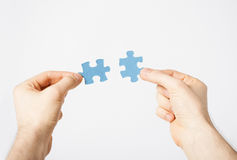Two hands trying to connect puzzle pieces. Close up of two hands trying to connect puzzle pieces Royalty Free Stock Images
