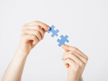 Two hands trying to connect puzzle pieces Royalty Free Stock Images
