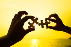 Two hands trying to connect puzzle pieces. With sunset background Stock Images
