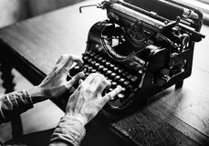 Two hands typing on retro typewriter