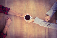 Two hands warming a cup of coffee Royalty Free Stock Photography