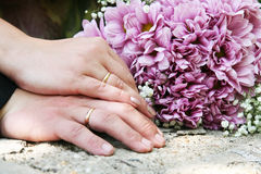 Two hands in wedding rings. On a background of a bouquet of chrysanthemums Royalty Free Stock Photos