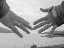 two hands with wedding rings and ocean in background - wedding anniversary, relationship, separation, breaking up