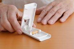 Pill tablet cutter knife hands Royalty Free Stock Photos