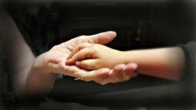 Two hands of young and old. Hand the old lady, holding the hand of a small child Stock Photos