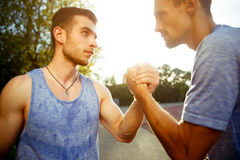 Two handsome athlete men handshake outdoors. Portrait of two handsome athlete men handshake outdoors on summer day. Focused on hands. Natural sunflare Stock Photography
