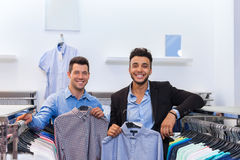 Two Handsome Business Man Fashion Shop, Happy Smiling Mix Race Friends Customers Choosing Clothes Shirts In Retail Store Stock Images
