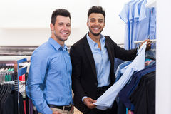 Two Handsome Business Man Fashion Shop, Happy Smiling Mix Race Friends Customers Choosing Clothes Shirts In Retail Store. Young People Shopping Formal Wear Stock Photo