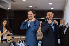 Two Handsome Business Men Wearing New Suits While Shopping In Modern Menswear Retail Store Stock Image