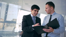Two handsome businessman discussing document. And secure an agreement with handshake stock footage