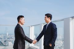 Two handsome businessmen greeting each other in the street.  royalty free stock images