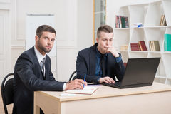Two handsome businessmen in office working on some Stock Photos